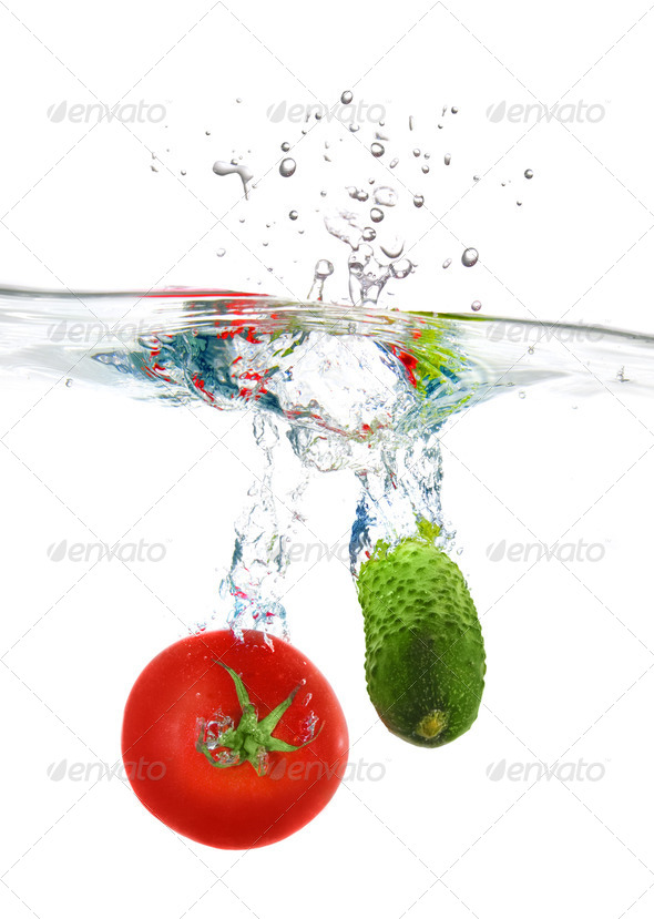 red tomato and green cucumber dropped into water isolated on whi - Stock Photo - Images
