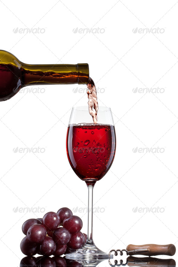 Red wine pouring into glass with grape isolated on white - Stock Photo - Images