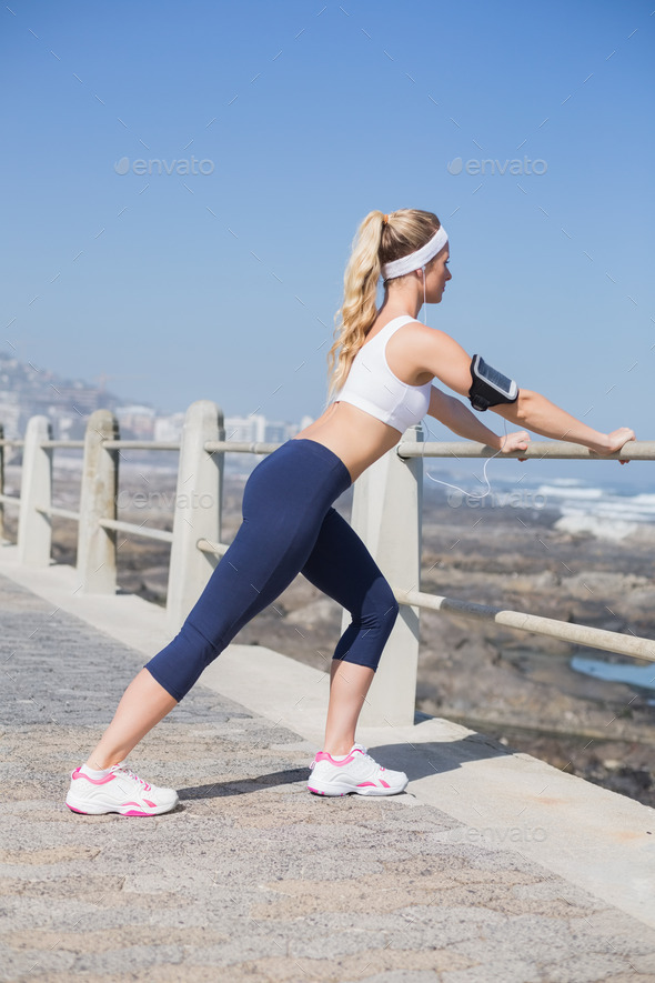 Fit blonde listening to music warming up on a sunny day - Stock Photo - Images
