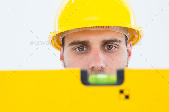Close-up of male technician using spirit level on white background - Stock Photo - Images