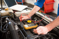 Mechanic using diagnostic tool on engine at the repair garage - PhotoDune Item for Sale