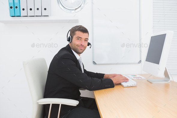 Businessman in headset smiling at camera in his office - Stock Photo - Images