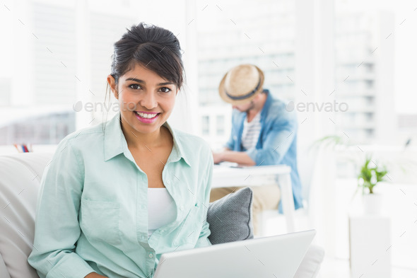 Cheerful businesswoman on couch looking at camera in the office - Stock Photo - Images