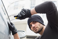 Thief breaking into car with screwdriver in broad daylight - PhotoDune Item for Sale