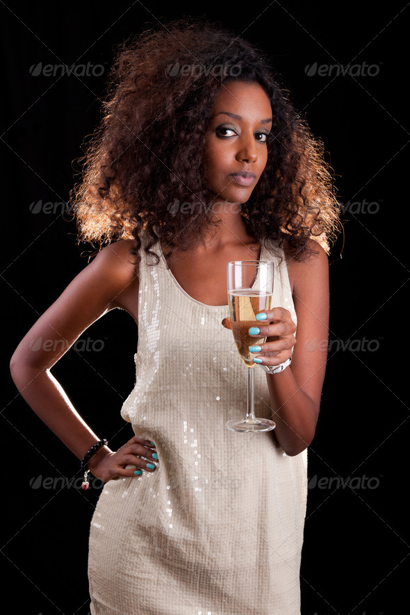Young beautiful African woman holding a glass of champagne - Stock Photo - Images
