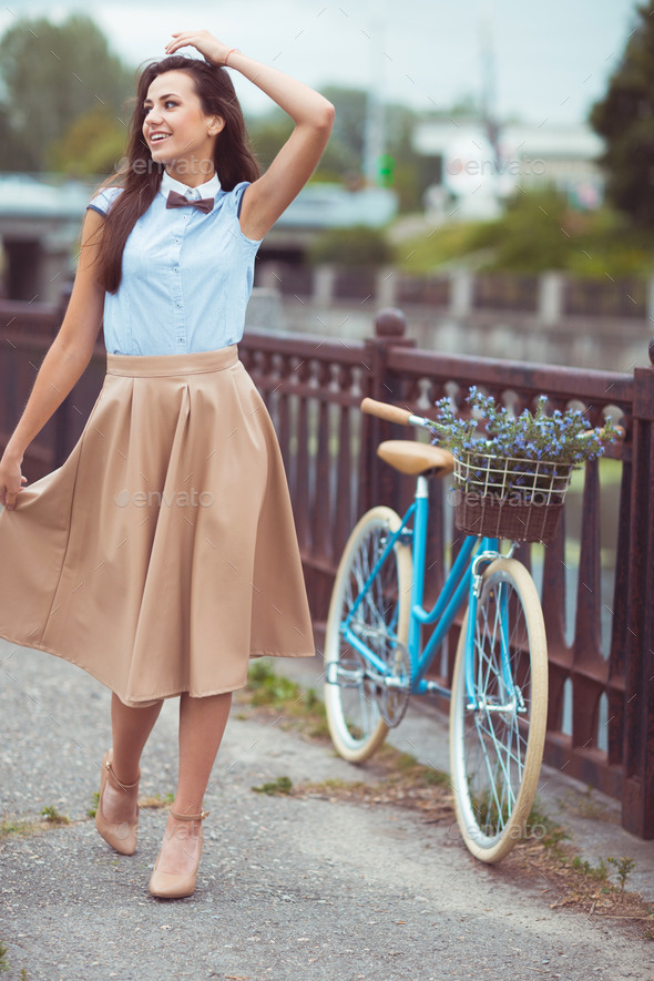 Young beautiful, elegantly dressed woman with bicycle in the par - Stock Photo - Images