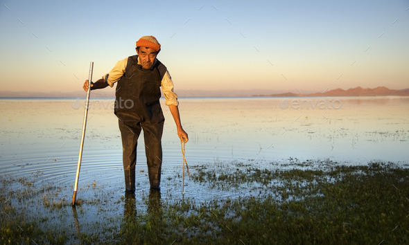 Mongolian Man Cleaning The Lake With The Cleaning Tool - Stock Photo - Images