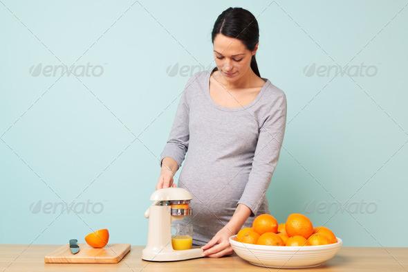 Pregnant woman making fresh orange juice. - Stock Photo - Images