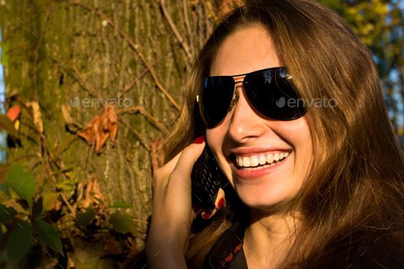Beautiful girl says on the mobile - Stock Photo - Images