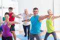 Happy men and women doing warrior pose in yoga class