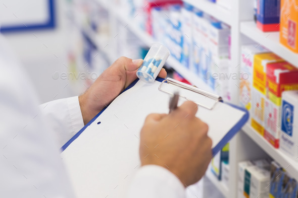 Pharmacist writing on clipboard and holding medicine jar at the hospital pharmacy - Stock Photo - Images