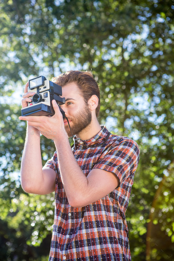 Handsome hipster using vintage camera on a summers day - Stock Photo - Images