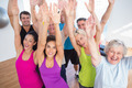 Portrait of cheerful friends with hands raised at fitness studio - PhotoDune Item for Sale