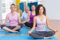 Fit women practicing lotus position in gym class