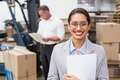 Portrait of smiling female manager holding files during busy period in warehouse - PhotoDune Item for Sale