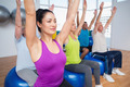 Fit people sitting on exercise balls with hands raised in fitness class