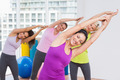 Portrait of happy women practicing stretching exercise in gym - PhotoDune Item for Sale