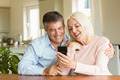 Happy mature couple looking at smartphone together at home in the kitchen - PhotoDune Item for Sale