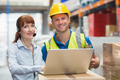 Smiling businesswoman wearing headset using laptop in warehouse - PhotoDune Item for Sale