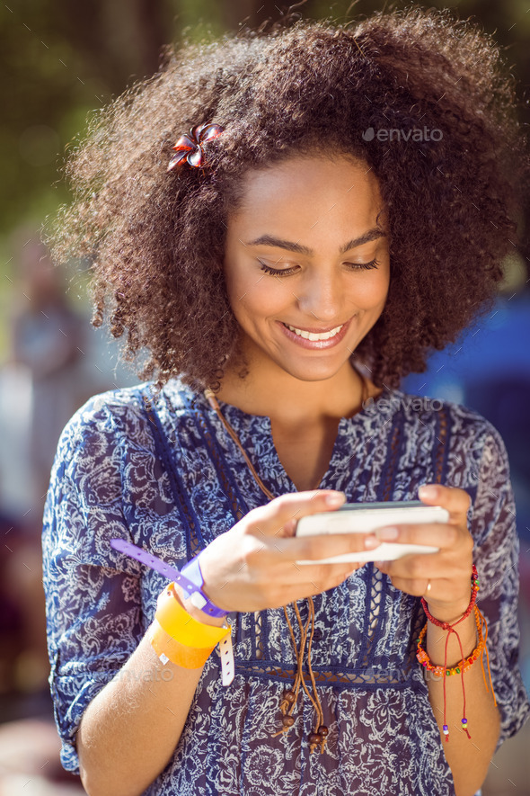 Pretty hipster looking at her selfie at a music festival - Stock Photo - Images