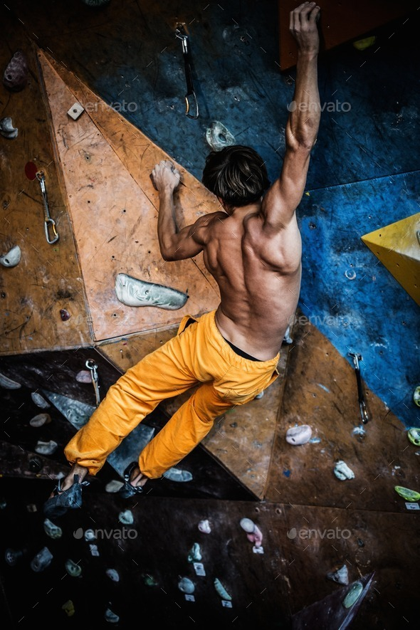Muscular man practicing rock-climbing on a rock wall indoors - Stock Photo - Images