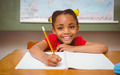 Portrait of cute little girl writing book in classroom - PhotoDune Item for Sale