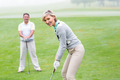 Lady golfer teeing off for the day watched by partner on a foggy day at the golf course - PhotoDune Item for Sale