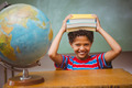 Portrait of cute little boy holding books over head in classroom - PhotoDune Item for Sale