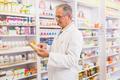 Smiling senior pharmacist reading prescription in the pharmacy