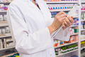 Pharmacist writing prescription on clipboard in the pharmacy