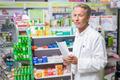 Senior pharmacist holding a prescription in the pharmacy