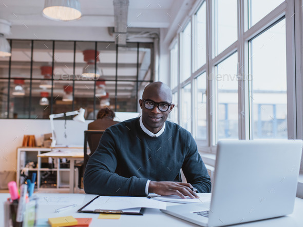 African businessman working in modern office - Stock Photo - Images