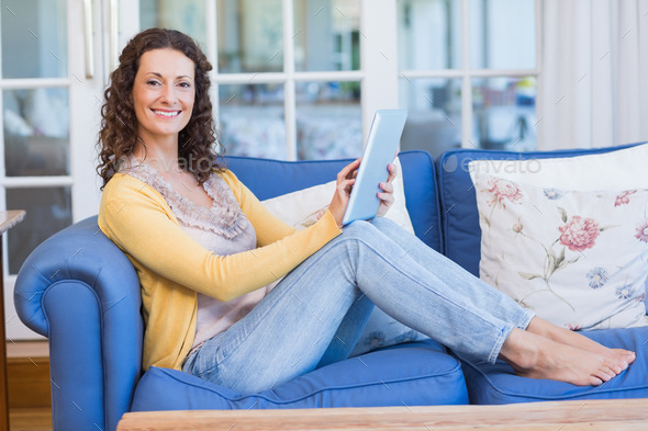 Pretty brunette relaxing on the couch with tablet in the living room - Stock Photo - Images