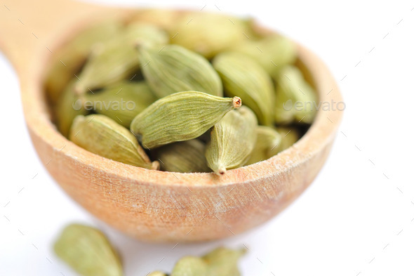 Cardamom seeds in the wooden spoon on white background - Stock Photo - Images