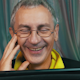 Laughing Man in Glasses Reading a Tablet