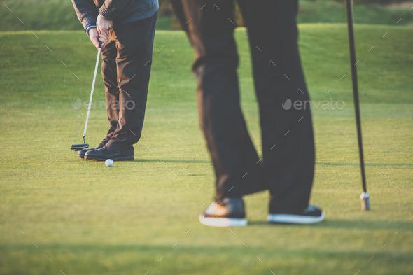 Golf green sceen - golfer putting near the hole, short putt - Stock Photo - Images