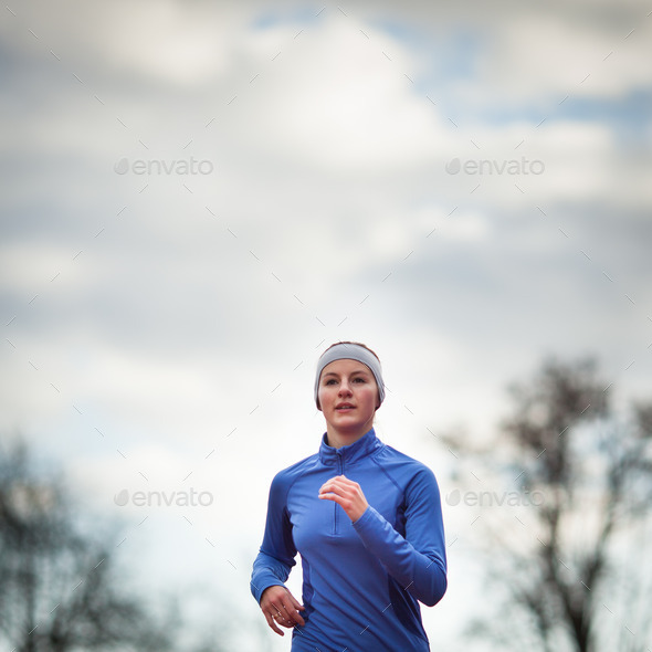 Portrait of a woman running against against blue sky - Stock Photo - Images