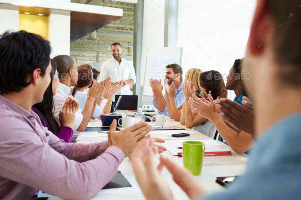 Businessman Addressing Meeting Around Boardroom Table - Stock Photo - Images