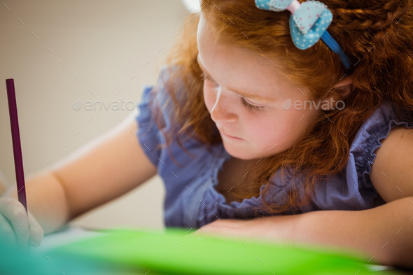 Pupil working hard at desk  at the elementary school - Stock Photo - Images