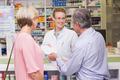 Pharmacist giving prescription to costumer at pharmacy