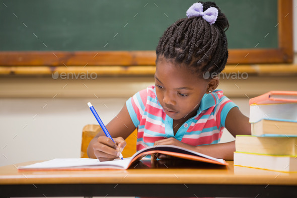 Cute pupils writing at desk in classroom at the elementary school - Stock Photo - Images