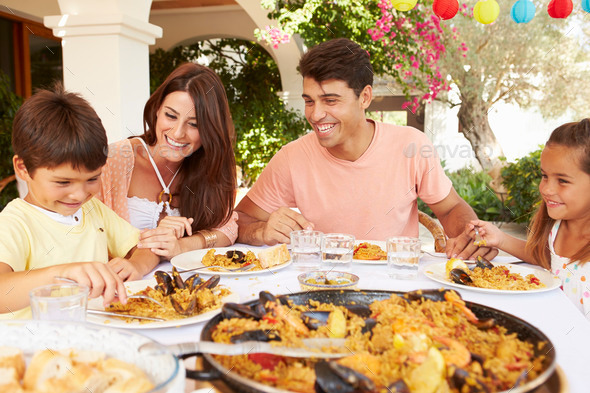Hispanic Family Enjoying Outdoor Meal At Home Together - Stock Photo - Images
