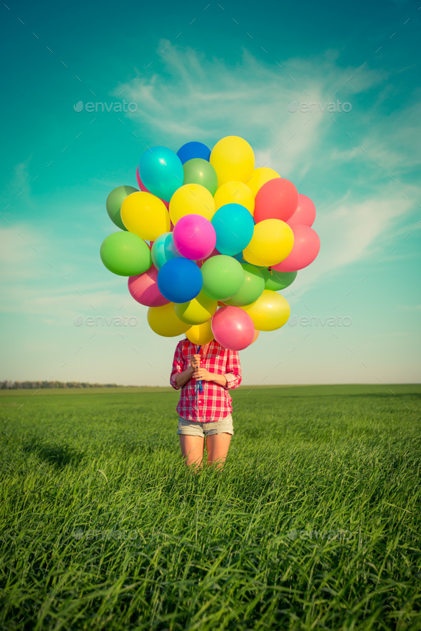 Woman with toy balloons in spring field - Stock Photo - Images