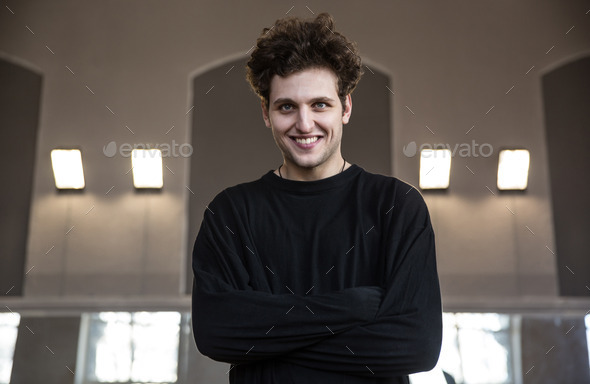 Portrait of a smiling young man with arms folded - Stock Photo - Images
