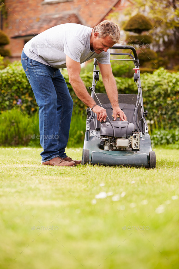 Man Working In Garden Cutting Grass With Lawn Mower - Stock Photo - Images