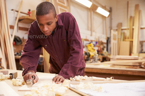Apprentice Planing Wood In Carpentry Workshop - Stock Photo - Images