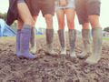 Close Up Of Friends In Wellington Boots Walking To Festival