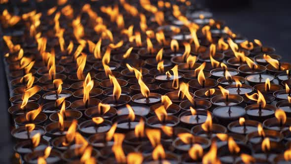 Multiple Ritual Candles Burning Next To a Buddhist Temple in Nepal. Slow Motion Close-up Shot