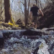 Hiker Walking in Nature through Stream - VideoHive Item for Sale