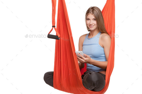 Young woman sitting in hammock for anti-gravity aerial yoga - Stock Photo - Images